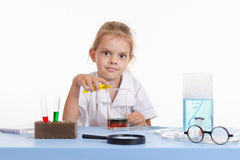 Mad Chemist pours yellow liquid in a flask Stock Image