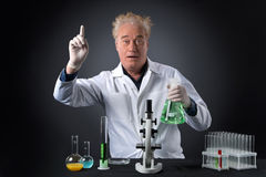 Mad clinician studies in laboratory and holding flask. Stock Photos