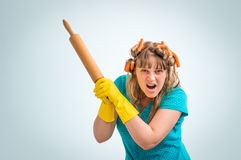 Mad and crazy housewife woman with kitchen roller Stock Images