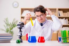 The mad crazy scientist doctor doing experiments in a laboratory. Mad crazy scientist doctor doing experiments in a laboratory Royalty Free Stock Photo