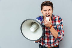 Mad crazy young man in plaid short shouting in megaphone. Over grey background Stock Image