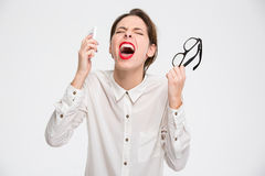Mad desperate business woman with smartphone and glasses  screaming Royalty Free Stock Photos