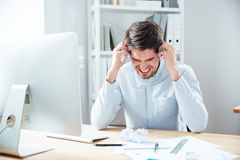 Mad desperated businessman sitting in office Stock Photo