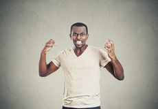 Mad displeased pissed off angry man arms in air screaming. Portrait mad displeased pissed off angry man arms hands in air screaming yelling  on grey background Royalty Free Stock Image