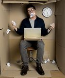 Mad employee is feeling annoyance at work. Under stress concept. Full length portrait of crazy businessman is looking at camera with rage. He is sitting in Royalty Free Stock Photography