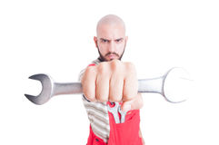 Mad and evil mechanic holding a big wrench Stock Photography