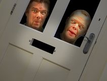 Mad faces peering through door Stock Photo