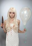 Mad girl. Young mad girl standing with balloon and knife in blood Stock Photo