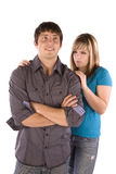 Mad girlfriend. A teen boy standing with a smirk on his face while his girlfriend with a dirty look on her face Stock Image