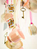 Mad Hatter Tea Party. Teacups, saucers, keys and cards hanging from ribbons stock image