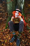 Mad Hatter and time. Mad Hatter sitting under a tree with an antique clock in his hands Royalty Free Stock Photos