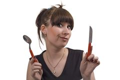The mad housewife with knife and spoon. Funny picture Royalty Free Stock Image