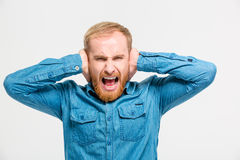 Mad hysterical man closed ears by hands and screaming Stock Images