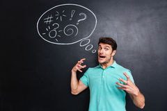 Mad irritated young man shouting over chalkboard background. Mad irritated young man standing and shouting over chalkboard background Royalty Free Stock Photo