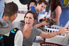 Mad in the Laundromat. Frustrated young woman yells at a man in the laundromat royalty free stock photo