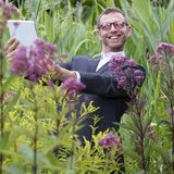 Mad male botanist making photos for his wild grass collection Stock Photography