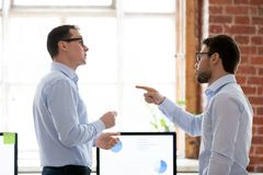 Mad male colleague blame coworker for business failure. Mad male colleagues have disagreement in office arguing on work issues, furious millennial employee point stock photo