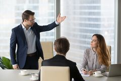 Mad male worker asking female partner leave meeting. Mad male worker gesturing asking female colleague leave business meeting, angry businessman standing showing royalty free stock image