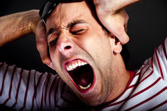 Mad man. Man holding head and screaming Stock Photo