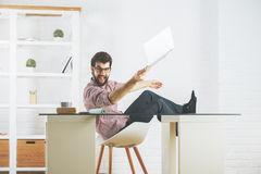 Mad man breaking laptop. Mad young man at workplace about to break his laptop. Stress concept Stock Photos