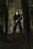 Mad man with chainsaw in the woods. Halloween and horror concept Stock Photos