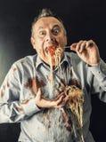 Man eating spaghetti with tomato sauce. Mad man eating spaghetti with tomato sauce Royalty Free Stock Image