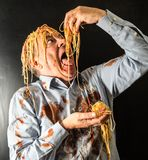 Man eating spaghetti with tomato sauce in head Royalty Free Stock Photography