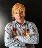 Man eating spaghetti with tomato sauce in head Stock Image