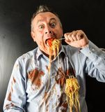 Man eating spaghetti with tomato sauce. Mad man eating spaghetti with tomato sauce Stock Photography