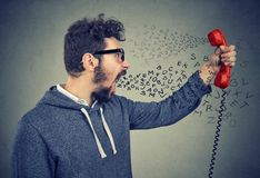 Mad man having angry conversation over the telephone. Side profile of an angry man screaming at someone on telephone handset with alphabet letters flying each Royalty Free Stock Photo