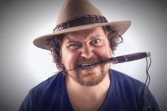 Mad man with knife between teeth Royalty Free Stock Photos