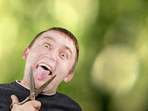 Mad man with scissors cuts off itself tongue on green background Stock Photography