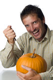 Mad Man Stabbing Pumpkin. A crazy looking mad man getting ready to stab a pumpkin with a sharp knife Royalty Free Stock Photography