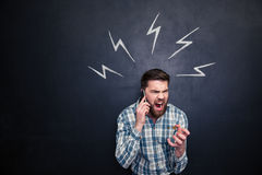 Mad man using cell phone and screaming over blackboard background. Mad hysterical young man with beard using cell phone and screaming over blackboard background Stock Photography