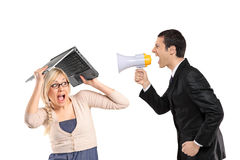 Mad man yelling via megaphone, woman covering. A mad businessman yelling via megaphone and woman covering his head isolated on white background Stock Photo