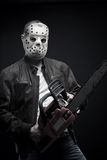 Mad maniac. Guy in mask with bloody chainsaw posing over dark background stock image