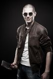 Mad maniac. Young man in sunglasses with bloody chopper posing over dark background royalty free stock images