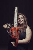 Mad maniac girl. Bloody maniac with chainsaw stands in empty dark room stock photography