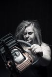 Madness. Mad maniac girl with chainsaw over dark background royalty free stock images