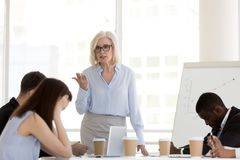 Mad mature businesswoman scolding employees for bad results. Angry mature businesswoman hold business briefing in office scolding young employees for bad work stock images