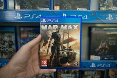 Mad Max. Bratislava, Slovakia, circa april 2017: Man holding Mad Max videogame on Sony Playstation 4 console in store Royalty Free Stock Images