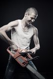 Mad mind. Angry man with bloody chainsaw posing over dark background royalty free stock photo