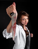 Mad nurse holds a bloody knife Royalty Free Stock Image