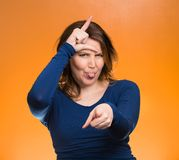 Mad pissed off woman, showing loser sign. Closeup portrait angry, mad pissed woman, showing loser sign, sticking tongue out, hand on forehead, isolated orange Royalty Free Stock Images