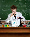 Mad professor. Shows attention gesture while working in his laboratory royalty free stock photo