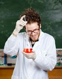 Mad professor adds something to the flask. With red liquid in his laboratory stock photos