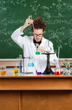 Mad professor conducts some chemical experiments. In his laboratory Royalty Free Stock Photo