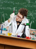 Mad professor examines a beaker. In his laboratory Stock Image