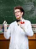 Mad professor laughs handing conical flask Royalty Free Stock Photography