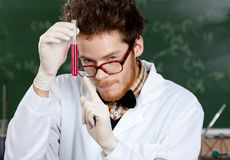 Mad professor points at the vial Stock Photos